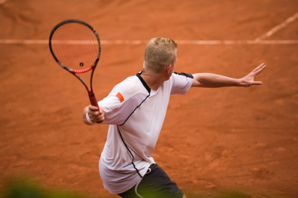 male tennis player in action on a clay court